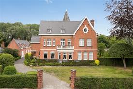 Landhuis met conciërge woning, bijgebouwen, stallingen te koop in Olsene!